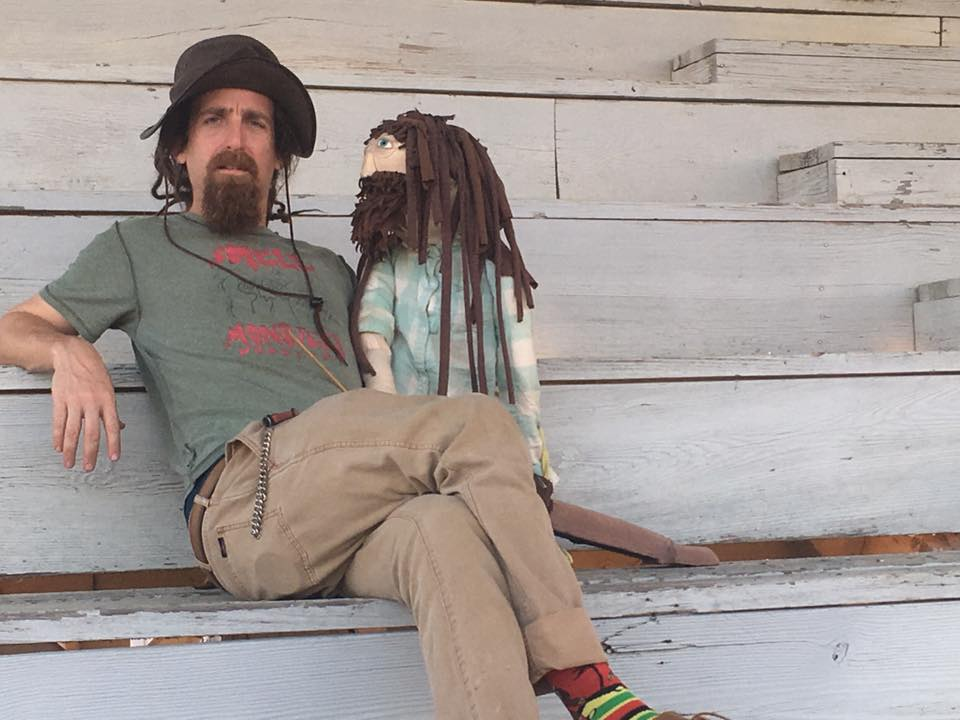"""A man wearing a hat, with a brown beard and dreadlocks, sits on a step wearing a shirt that says """"Smell Monsters Puppetry"""" and holding a puppet version of himself."""