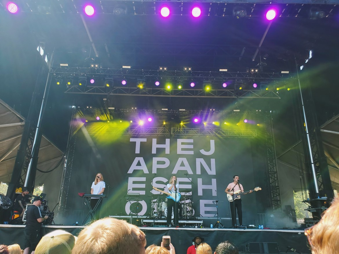 The Japanese House Performing at the VRBO stage at ACL. Amber Bain is in the center, with a keyboardist to her right and a guitarist to her left.