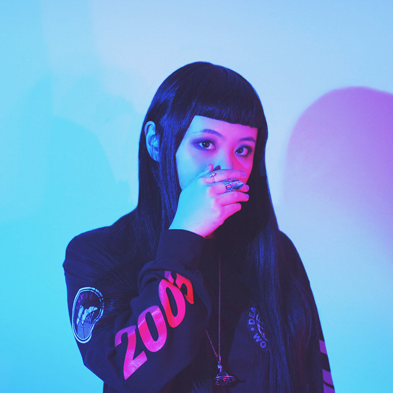 A young woman who is covering her mouth standing against a plain background. The picture is lit with pink and blue lights.