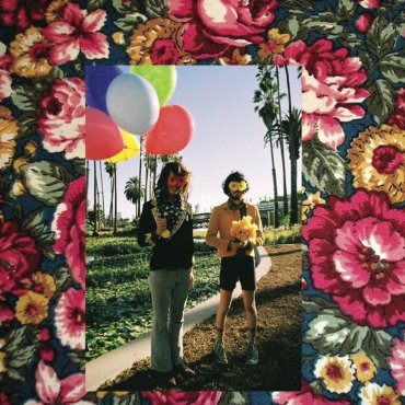 A picture of two men standing on mulch with one carrying flowers, the other balloons surrounded by a border of flowers