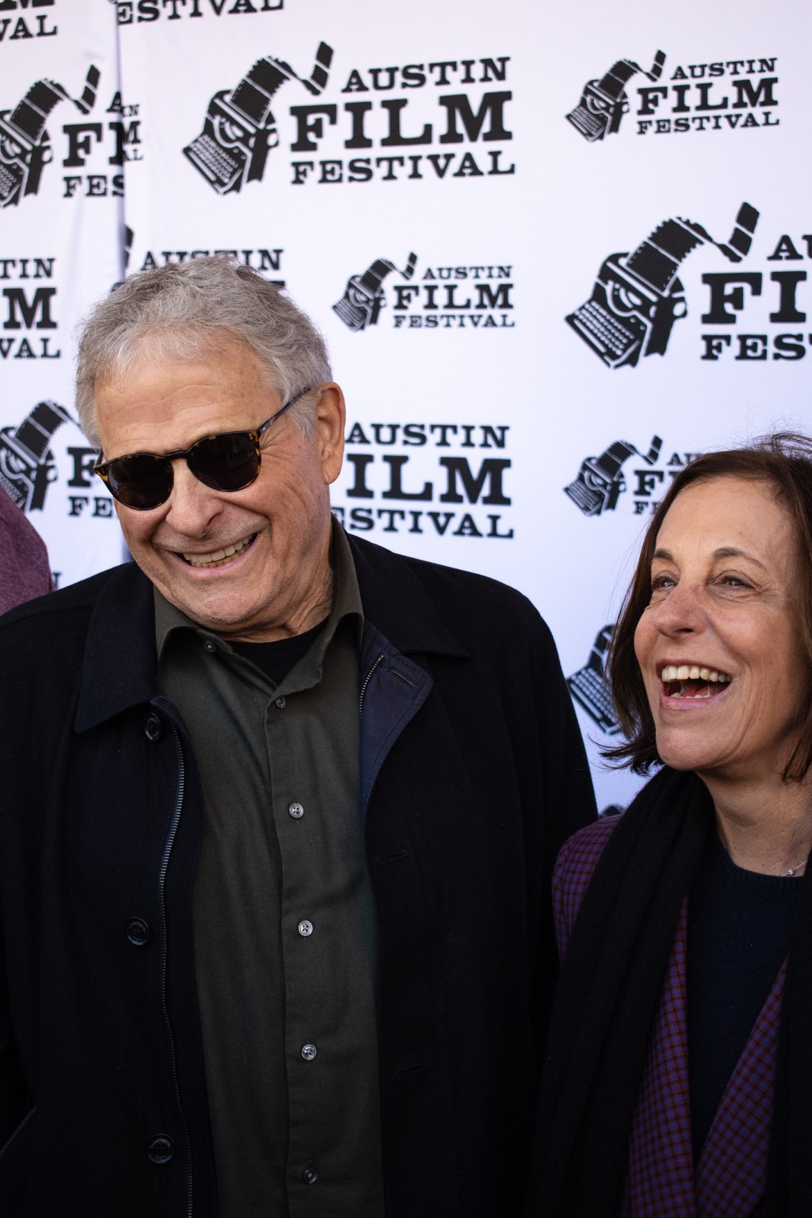 Man (left) and woman (right) laughed together during an interview on the red carpet.