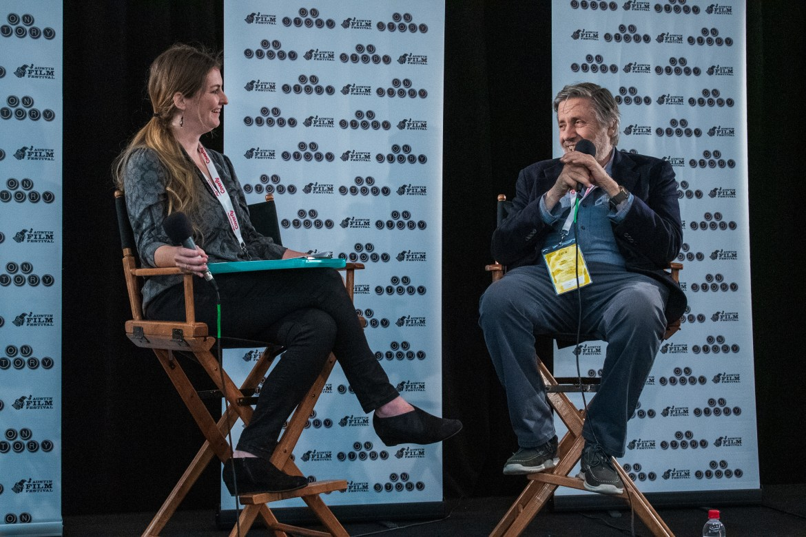 Lady sitting in a directors chair on the left. Man sitting in a directors chair on the right. Both holding mics to speak.