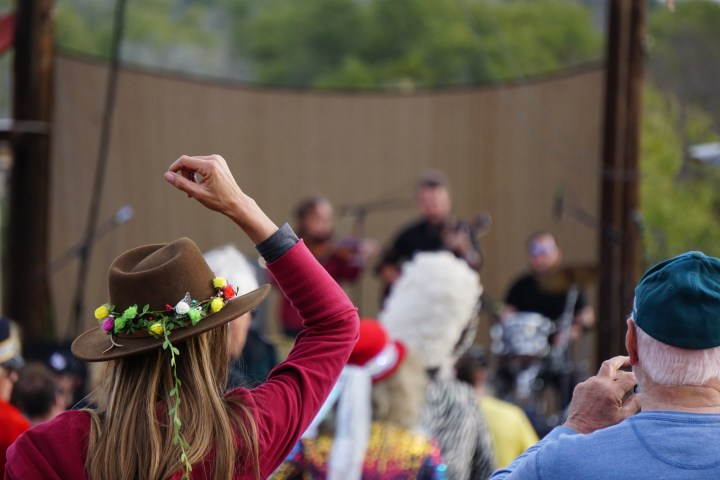 A woman in a brown hat wrapped with flowers puts her right hand up while listening to the Jon Stickley Trio