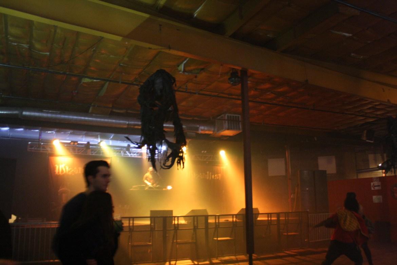 A shrunken head made of paper hangs above a dj booth.