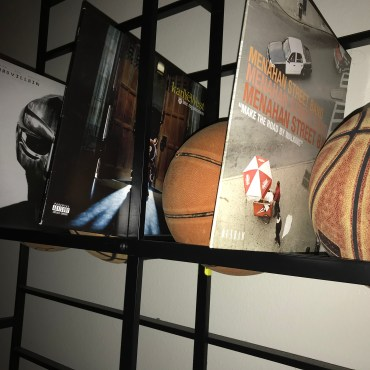 Three Basketballs lined up on a rack with records between them.