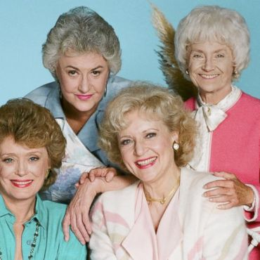 A photo showing Bea Arthur and Estelle Getty smiling and leaning over a grinning Betty White and Rue McClanahan.