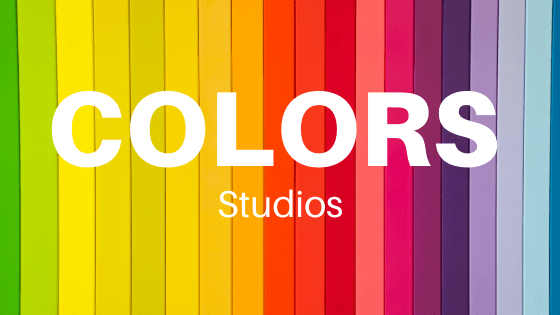 """A background with block coloring in rainbow order from green, yellow, red, orange, pink, purple and blue with the word """"colors"""" in white block lettering in all caps and """"studios"""" directly underneath it in smaller font."""