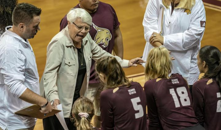 Karen Chisum and her assistant coaches stand in front of four Bobcat volleyball players in maroon jerseys with white lettering and numbers on the sideline in a match at Strahan Arena.