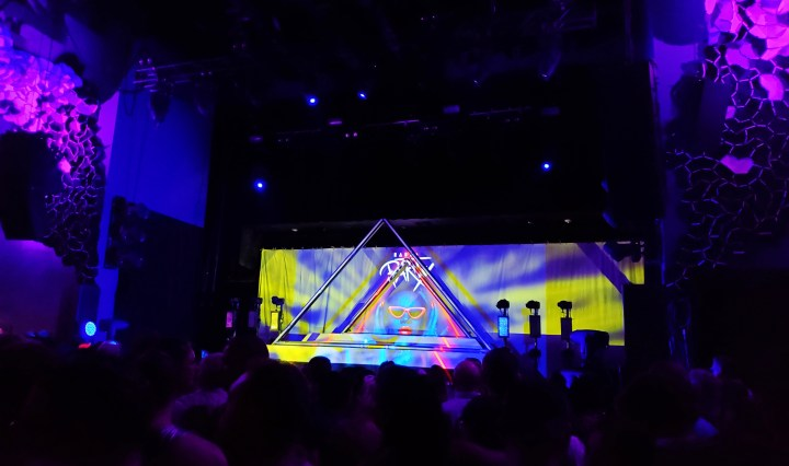 """A picture of Emo's stage. The lighting is purple, and the backdrop on the stage in a picture of Todrick Hall with red lips and sunglasses with the words """"Haus Party"""" written above his head. There are two triangular fixtures on the stage."""