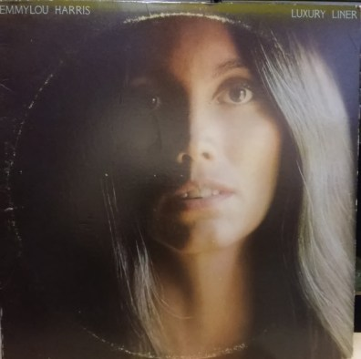 The face of the artist, Emmylou Harris, is the predominant image in this artwork. The name of the artist is in the top left of the image, the album title in the top right