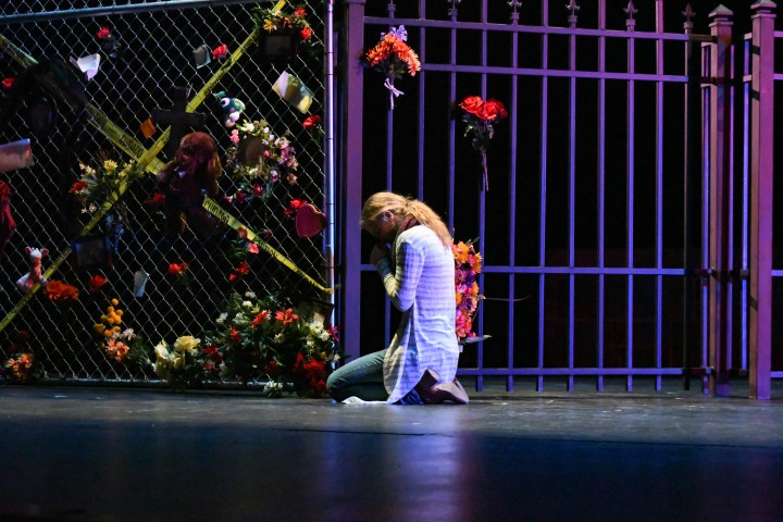 Woman cries by metal fence with flowers.