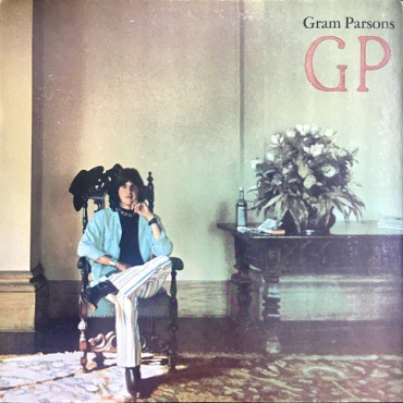 """Gram Parsons sits in an ornate chair beside a table with a large bouquet of flowers and what appears to be a wine bottle placed on top of it. The artist is wearing a blue shirt, white pants and is sitting with his leg crossed. The album's title, """"GP,"""" sits in the top right hand part of the image, with the artist's name placed right about it."""