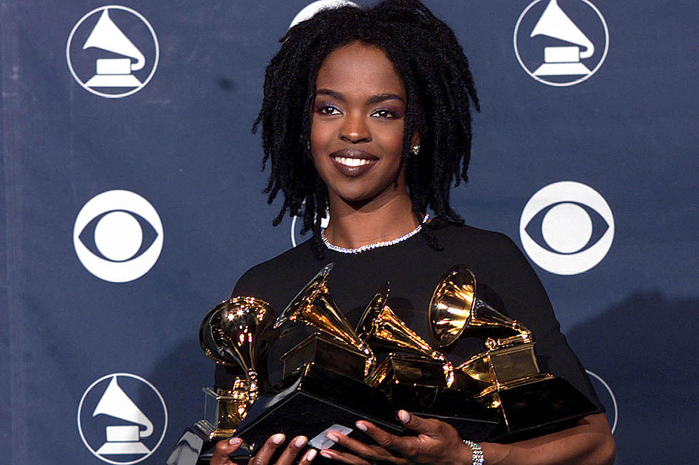 This is a picture of the rapper and songwriter, Lauryn Hill holding the five Grammys that she won at the 1999 Grammy Awards.