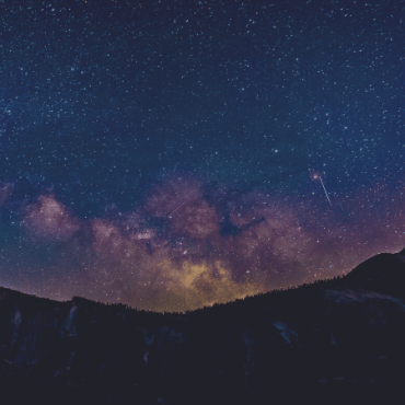 Purple clouds peek out from behind a mountain range in the night sky.