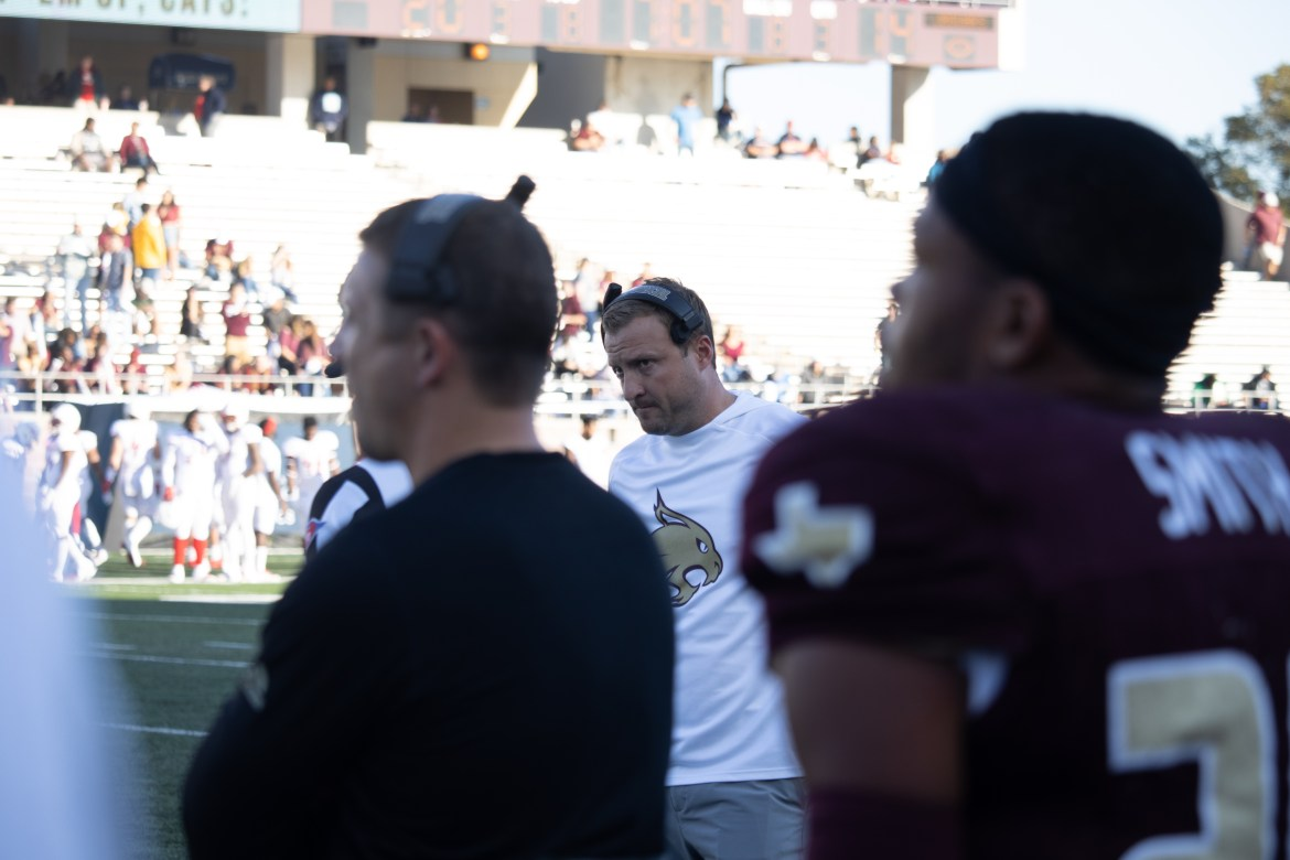Jake Spavital is between a football player and a coach in the photograph on the sideline.