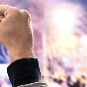 A closed fist being held up against a blurry background at night with white, pink, purple, blue, and yellow lights.