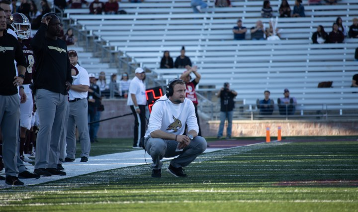 The football coach is squatting on the sidelines of the green football field. He is wearing a white long sleeve shirt with a gold bobcat logo in the middle