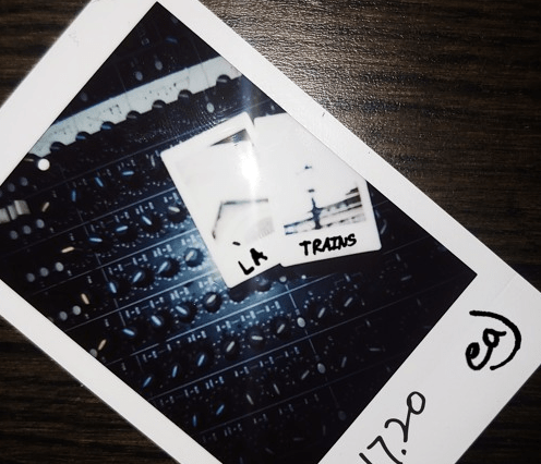 """The album cover for """"LA Trains"""" by eaJ Alt-text: There is a polaroid of the soundboard with two blurred out polaroids sitting on top of it. The two polaroids have LA Trains written on them in sharpie. And the larger polaroid has the date 01.17.20 and eaJ written on it in sharpie."""