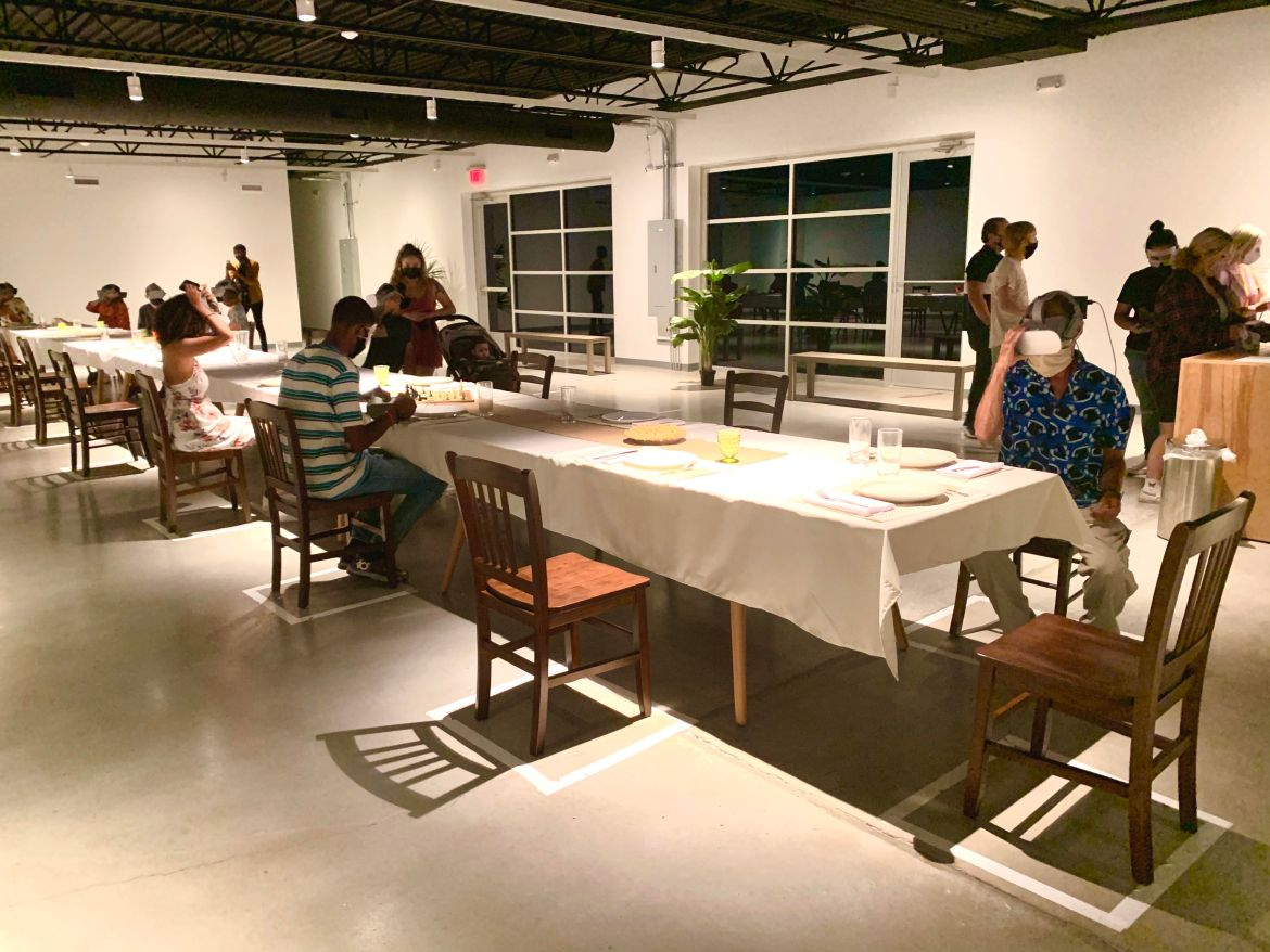 Visitors at Wonderspace sitting at a dinner table with VR headsets on