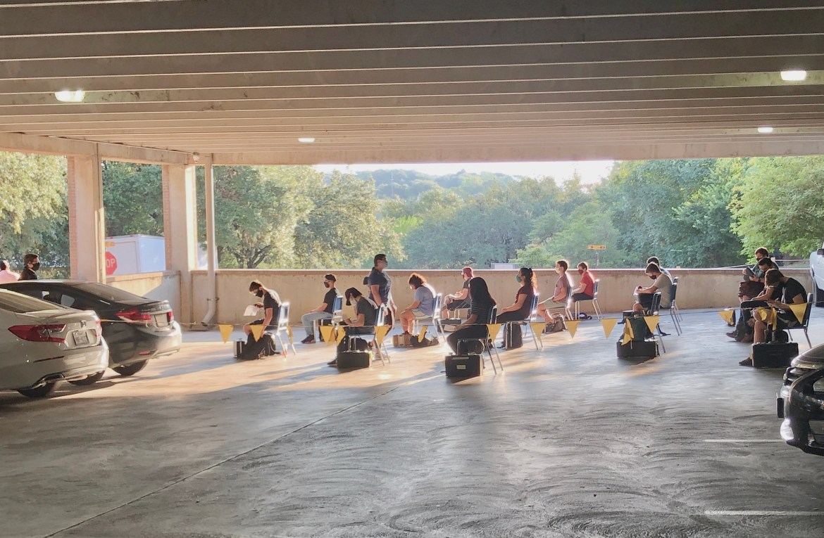 A photograph of students of a School of Music course participating in classwork in a reserved area of the Pleasant Street parking garage. Featured in the image are various students seated in classroom chairs and with instruments by their sides.