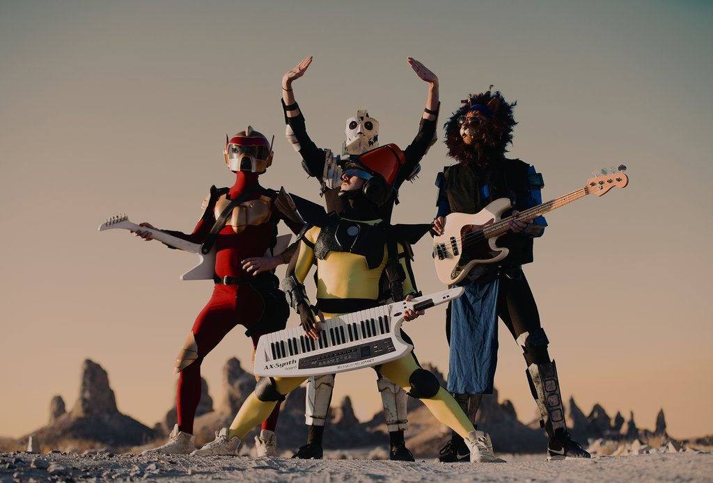 The four members of TWRP, Lord Phobos (top-left), Havve Hogan (top-center) Commander Meouch (top-right), and Doctor Sung (bottom-center). Each member is wearing a unique solid-colored outfit and mask in accordance with their on-stage persona. All members are posing victoriously in front of a mountain landscape.