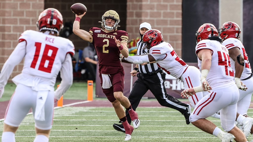 Texas State quarterback Brady McBride is throwing a pass while being pursued by Arkansas State defenders.
