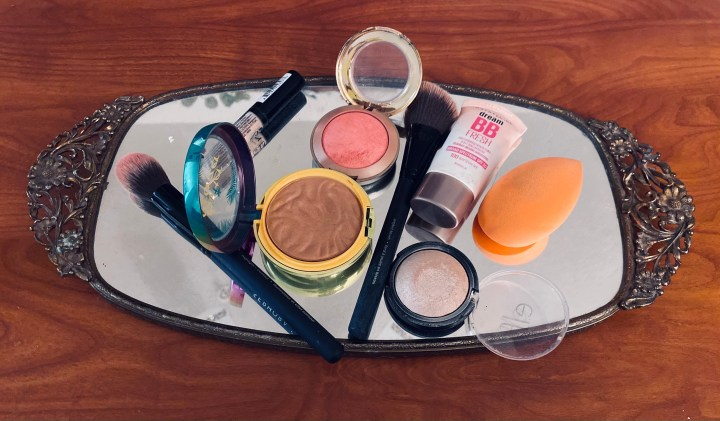 Face makeup products on mirror tray
