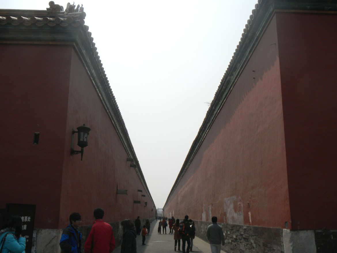 The tall and red hallways inside the Forbidden City. People walk along the stretching hallways into the distance.