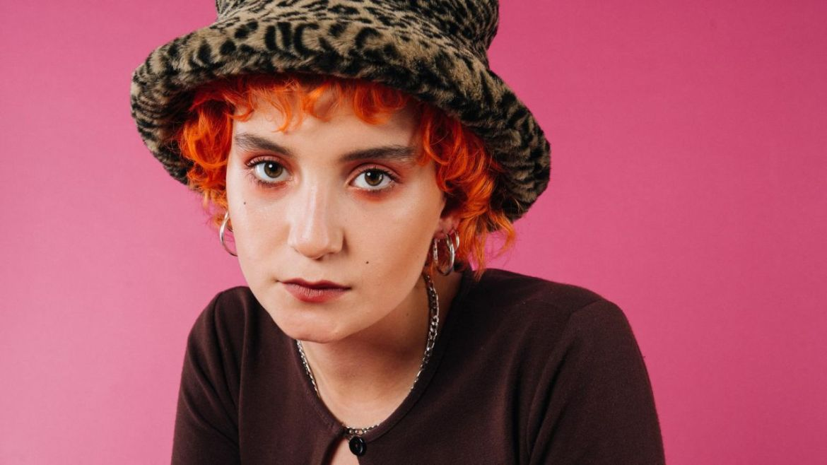 Portrait photo of Phoebe Green in a leopard bucket hat in front of a pink backdrop. Phoebe's hair is orange and curly.