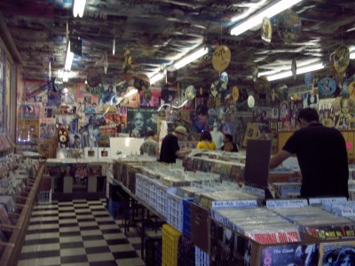 The interior of Sundance Records is covered from head to toe in newspaper clippings, local artwork, and tour posters.