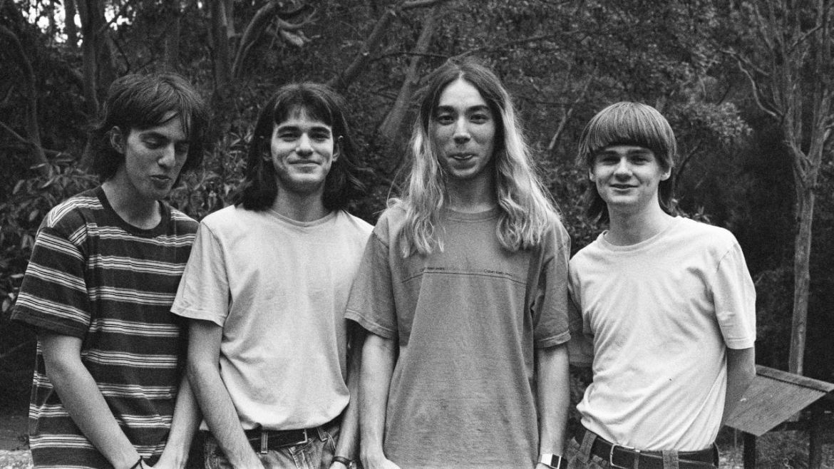 Black-and-white image of band members, 4 long haired men, smiling.