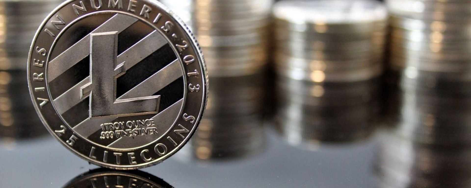 A photo of a silver coin with an L on it with diagonal lines behind it stands on its side. The coin has the text: Veres In Numeris 2013 – 25 Litecoins. In the background is a blurred vision of other silver coins stacked onto one another