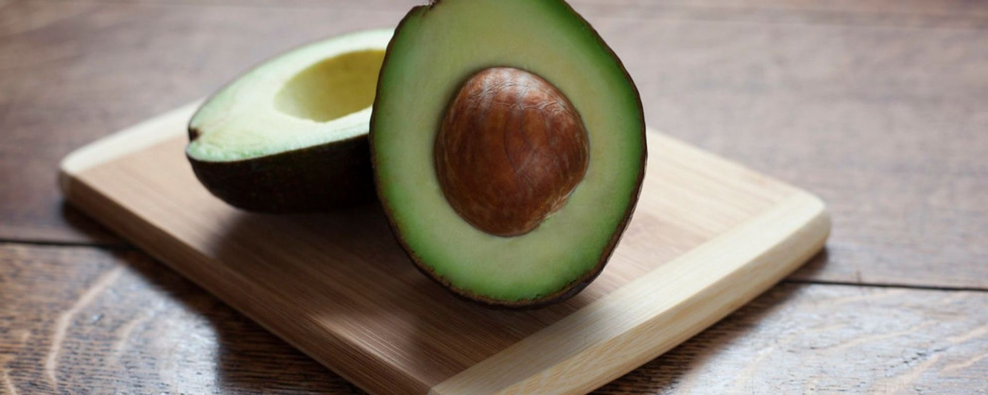 A photo of an avocado sliced in half sitting on a cutting board on top of a wood table.