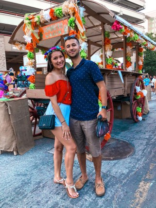 A young couple pose holding onto one another smiling at the camera in front of a sombrero wagon.