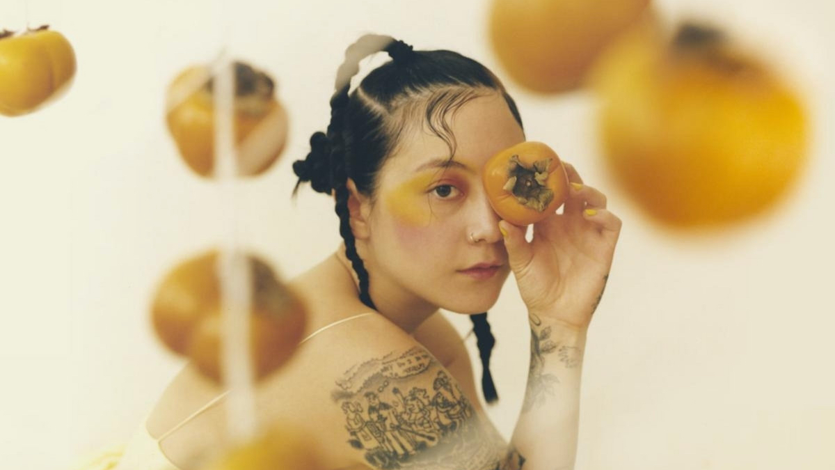A picture of Michelle Zauner of Japanese Breakfast, clothed in yellow with yellow decor and accessories.
