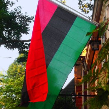 A photo of a red, black, and green flag hanging off the side of a brick building with trees in the background as well as power lines.