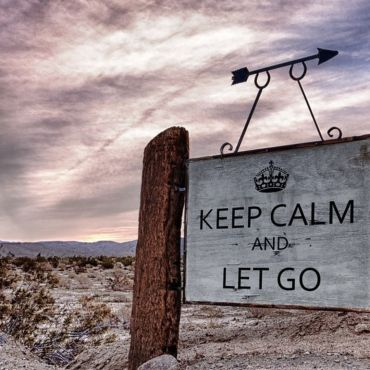 A photo of a white sign that says Keep Calm and Let Go. The sign has two wood pillars on each side holding it up. The sign also has an arrow attached to the top of it, pointing right. In the background is a grey sky with mountains in the distance. The setting is in a desert, with white dirt all around and tiny brown bushes.