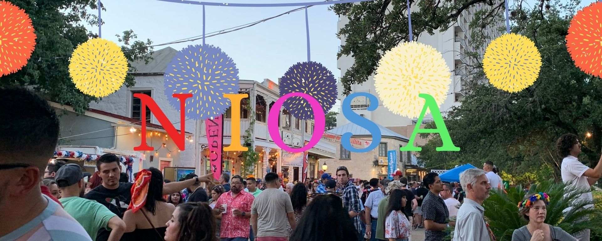 A crowd of people at the festival with the text NIOSA in colorful lettering with colorful pom poms going across the top.