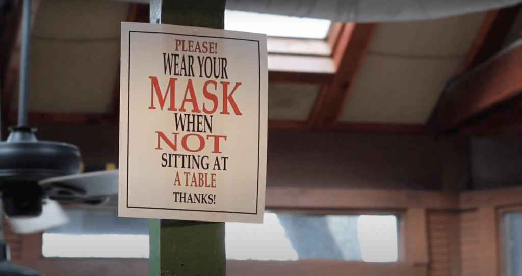 A photo of Grins Restaurant with a sign enforcing a mask rule