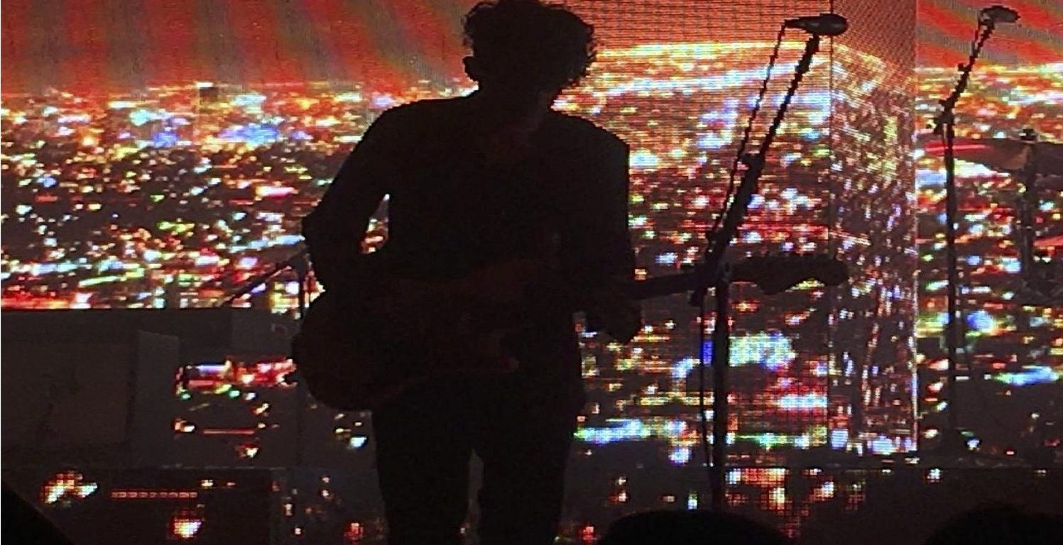 """The photo is a live performance of the lead singer's shadow playing guitar and the drumist playing the drums with a projected background of city lights at night. he 1975 performing their song """"Medicine"""" in Austin, Texas in 2017"""