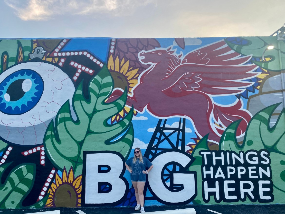 """picture of me between the """"b"""" and """"g"""" of the mural"""