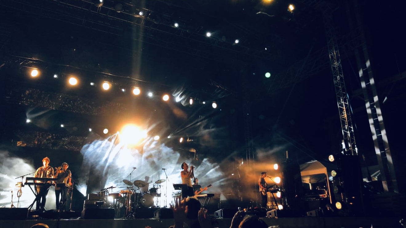 A picture of a band performing on an outdoor stage at night with stage lights shining down.