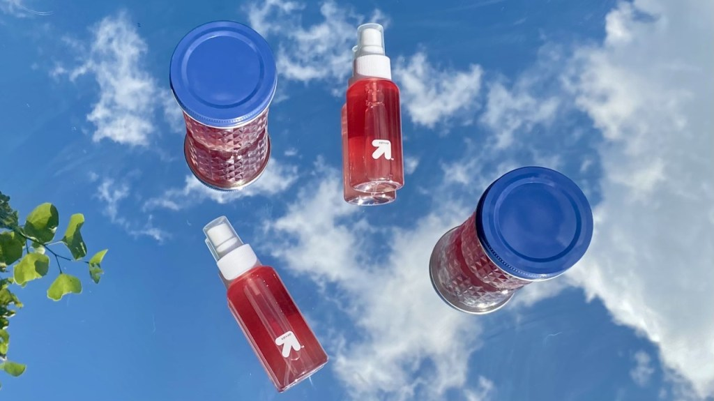 Image of two spray bottles and two mason jars filled with rosewater with the sky in the background