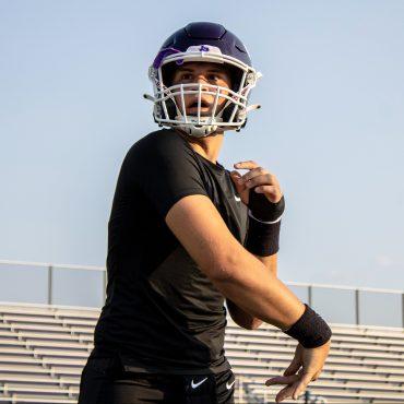 San Marcos High School football player in a black shirt and purple helmet throws through a pass