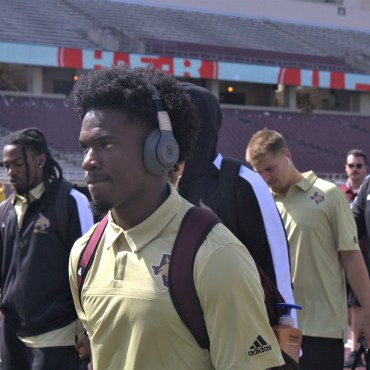 Bobcat football player in gold walking with his team on the field to the locker room before the game