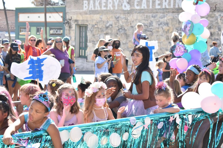 A group of little girls in costume wave from their parade float at the people.