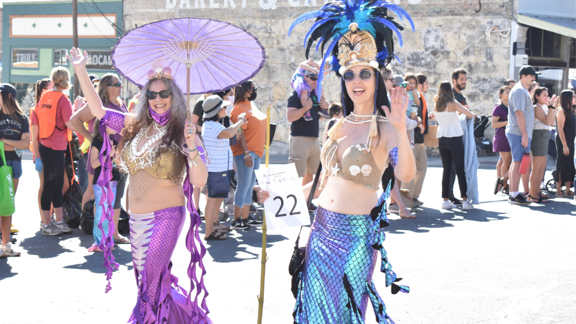 Two women dressed as mermaids, one in mostly purple and the other in blue, smile and wave at the parade-goers.