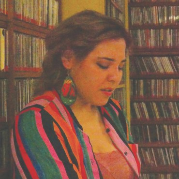 A young feminine person standing and looking down at the ground, in the middle of a room of CDs and records that is the background.