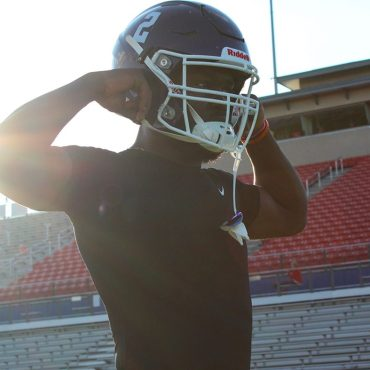 San Marcos High School football player wearing a black shirt and purple helmet flexing his muscles in front of Westlake's red and silver football stadium.