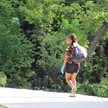 : A woman holding a bag of trash over her shoulder and walking on a sidewalk in Rio Vista Park